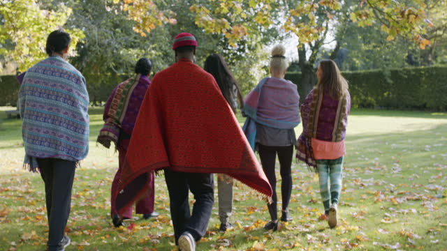 yoga students walking towards corner of park wrapped in blankets - moving after stock videos & royalty-free footage