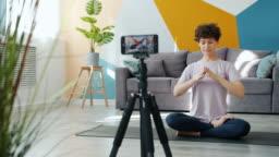 Yoga teacher recoding video doing asanas meditating talking in modern apartment