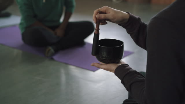 Yoga teacher uses sound bowl