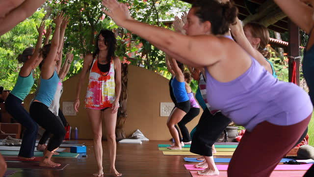 a yoga teacher/woman walks towards the camera as she directs an outdoor yoga class of women to recline back into chair position with their hands up in the air, surrounded by lush vegetation - kelly mason videos stock videos & royalty-free footage