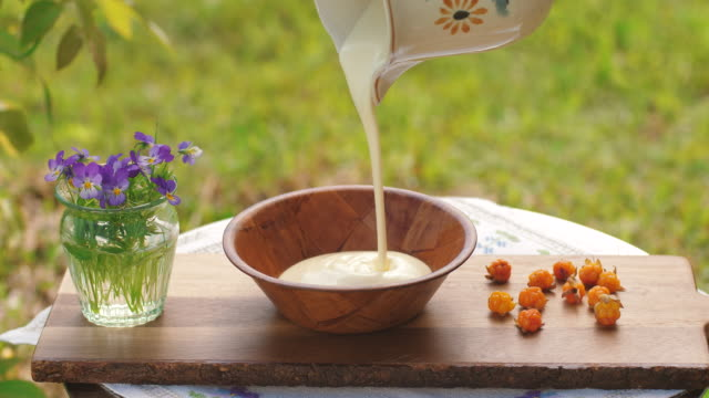 yoghurt and cloudberries served in the garden - pouring stock videos & royalty-free footage