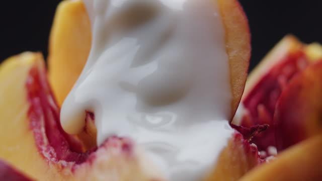 ヨーグルトは新鮮な桃のスライスに注いでいます。極端なクローズアップ - モモ点の映像素材/bロール