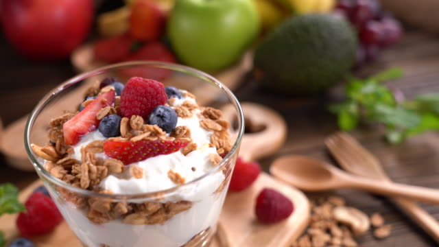yogurt with granola and fruits in glass on wooden table - yoghurt stock videos & royalty-free footage