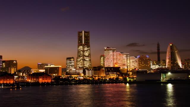yokohama minato mirai buildings light up and m't fuji time lapse at dusk - yokohama stock videos and b-roll footage