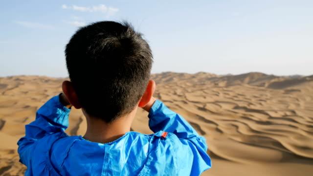 yong boy looking with binoculars in desert - standing stock videos & royalty-free footage