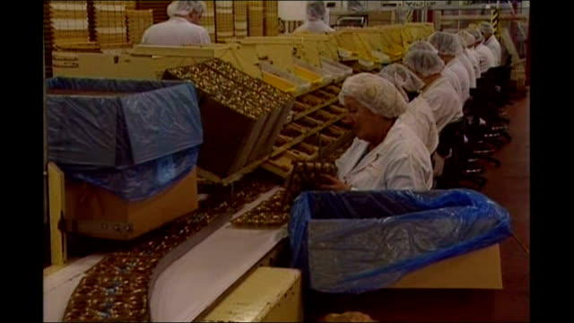 stockvideo's en b-roll-footage met york int women workers packing chocolates on terry's production line ext 'terry york' sign on clock tower outside terry's factory - kraft