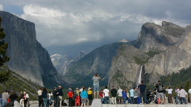 yosemite crowds at tunnelview photographing & looking at bridalveil fall, el capitan & half dome in yosemite national park, california - yosemite national park stock-videos und b-roll-filmmaterial