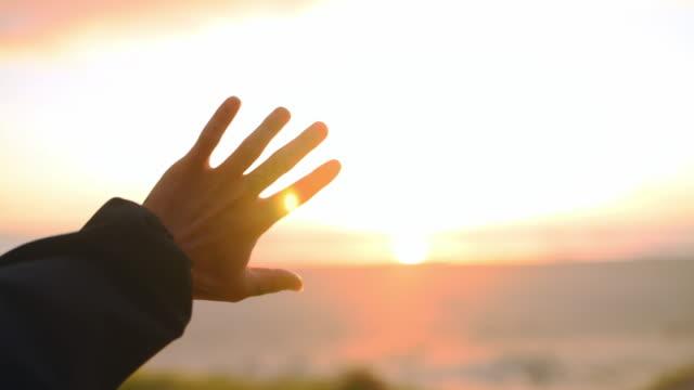 太陽の暖かさを感じることができる - human hand点の映像素材/bロール