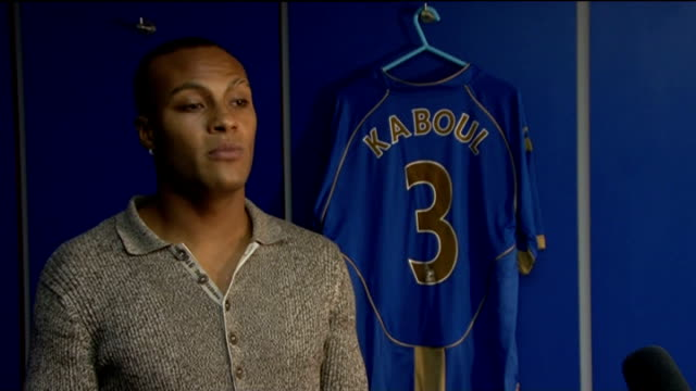 younes kaboul signs for portsmouth; england: portsmouth: fratton park: int younes kaboul sitting in front of portsmouth fc shirt with his name on... - ハリー レッドナップ点の映像素材/bロール