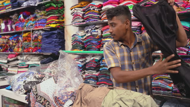 a young 20-years-old muslim man, a seller, is working in a small clothes shop in sri lanka, makes an order on shelves - sri lankan culture stock videos & royalty-free footage