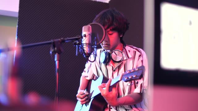 vidéos et rushes de jeune chanteuse acoustic enregistrement de musique avec la guitare dans le studio, concept de studio d'enregistrement - singer