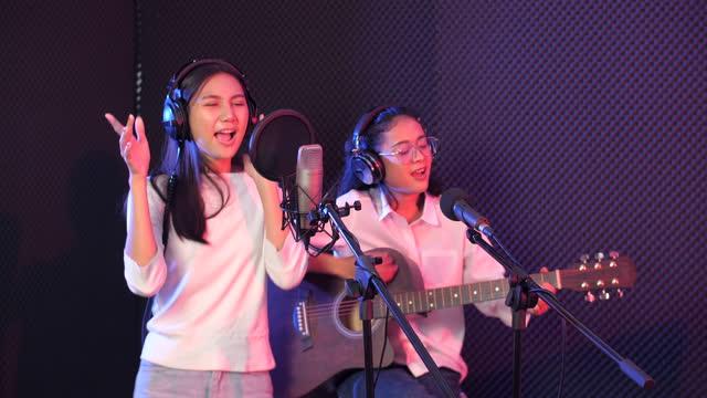 vidéos et rushes de jeune chanteur acoustique de femelles enregistrant la musique avec la guitare dans le studio, concept de studio d'enregistrement - singer