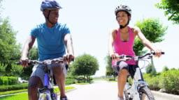 Young active African American couple enjoying biking outdoor