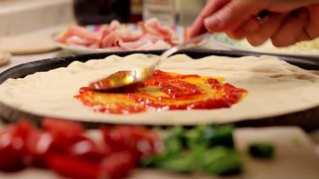 Junger Erwachsener hinzufügen Tomaten-Salsa auf Pizzateig