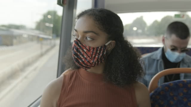 young adult afro american woman sitting on the bus wearing face mask during coronavirus pandemic - commercial land vehicle stock videos & royalty-free footage