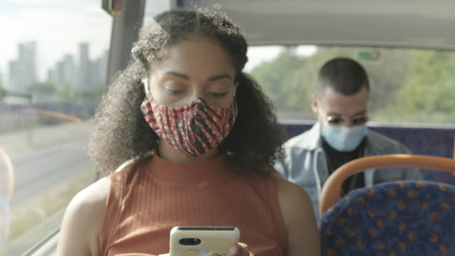 young adult afro american woman sitting on the bus wearing face mask during coronavirus pandemic - generation z stock videos & royalty-free footage