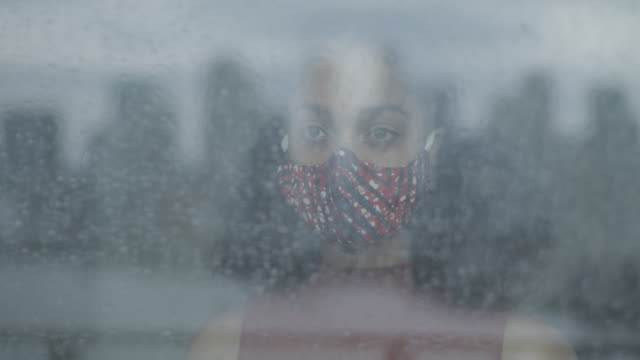young adult afro american woman wearing protective face mask during lockdown social distancing and looking trough window at gloomy sky in the rain during coronavirus pandemic - tranquility stock videos & royalty-free footage