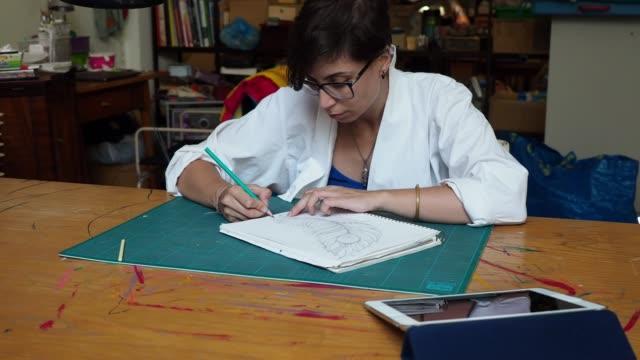 Jungen Erwachsenen Künstler Zeichnung eine Feder mit einem Bleistift