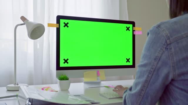 vídeos de stock, filmes e b-roll de adulto novo em sua mesa trabalha em um computador com tela verde mock-up. sobre a filmagem do ombro. ela senta-se na mesa em casa. - modelo web