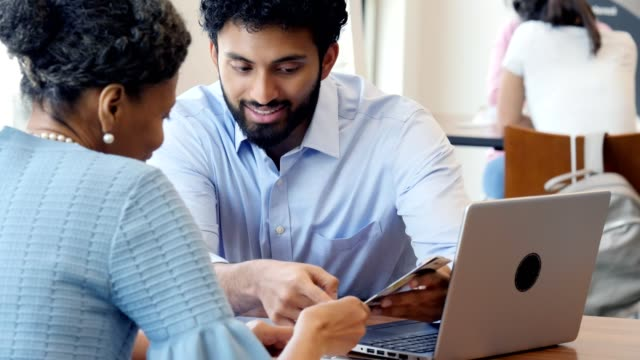 Jonge volwassen bank werknemer bespreekt rekeningen met vrouwelijke klant