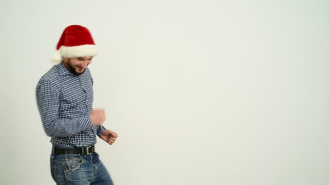 young adult beard man dancing in a hat santa claus on a grey background - santa hat stock videos and b-roll footage