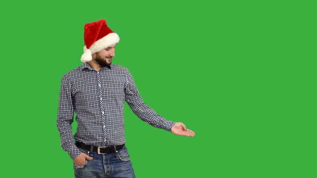 young adult  beard man showing an copy space and showing a thumb  in a hat santa claus  on a green background - santa hat stock videos and b-roll footage