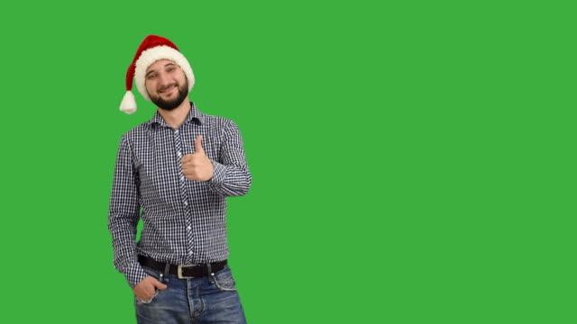 vídeos de stock e filmes b-roll de jovem adulto barba homem mostrando uma cópia espaço e mostrando o polegar em um chapéu de santa natal em fundo verde - chapéu do pai natal
