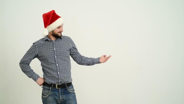 vídeos de stock e filmes b-roll de jovem adulto barba homem mostrando uma cópia espaço em um chapéu de santa natal sobre um fundo cinzento - chapéu do pai natal
