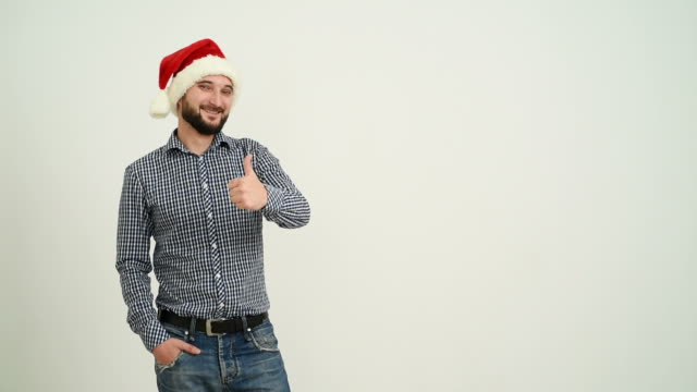 young adult beard man showing an copy space  in a hat santa claus on a grey background - santa hat stock videos and b-roll footage