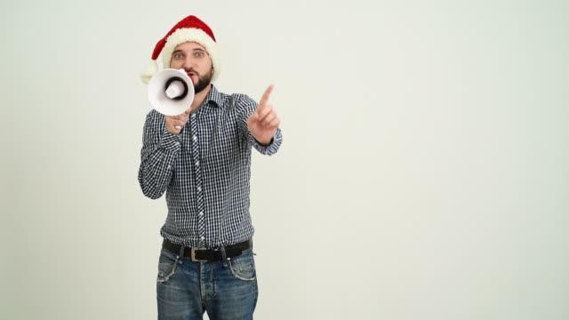 vídeos de stock e filmes b-roll de jovem adulto barba homem mostrando uma espaço de cópia com megafone em um chapéu de santa claus sobre um fundo cinzento - chapéu do pai natal