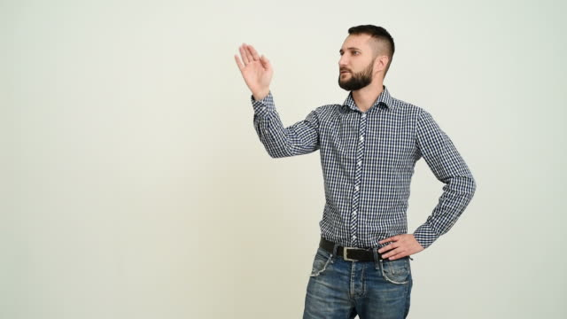 young adult beard man shows copy space  on a gray background - plaid shirt stock videos & royalty-free footage