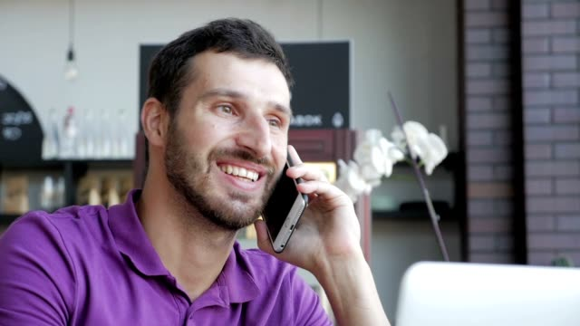 young adult bearded man talking on smartphone in cafe - phone message stock videos & royalty-free footage