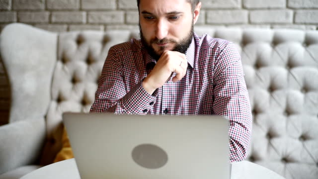 young adult bearded man with a laptop