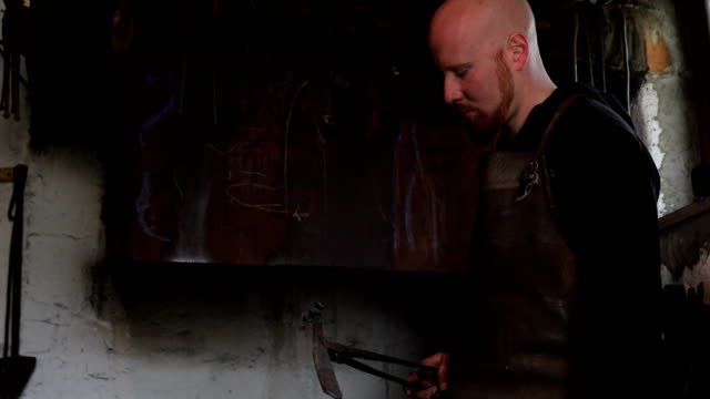 Young Adult Blacksmith Looking at his Incomplete Knife