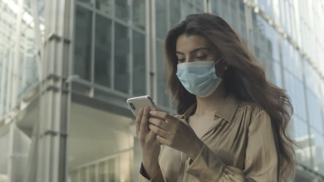 young adult business woman commuting in city wearing protective face mask and using mobile phone on the move during pandemic - blouse stock videos & royalty-free footage
