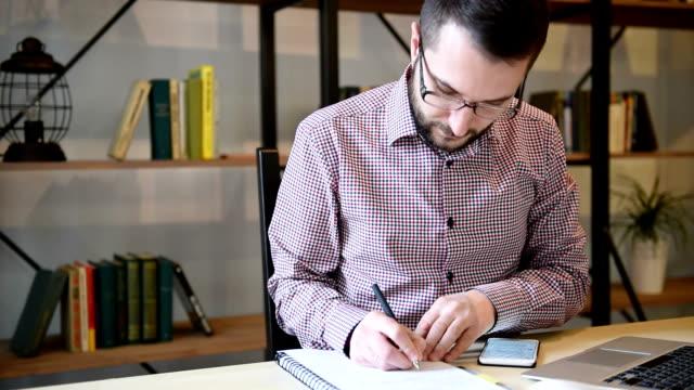 giovane adulto uomo d'affari al lavoro in ufficio - archivista video stock e b–roll