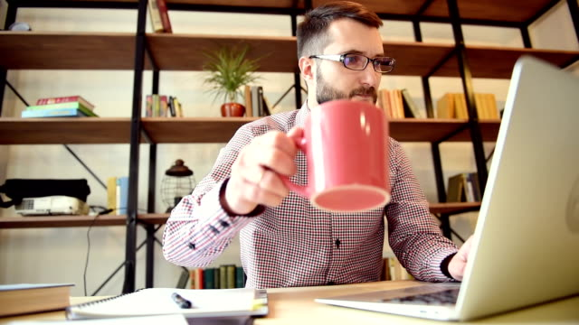 vídeos de stock, filmes e b-roll de adulto jovem empresário trabalhando no computador portátil e bebendo algo - coworking space