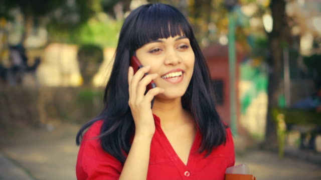 young adult businesswoman uses smartphone at day time in park. - south asia stock videos & royalty-free footage