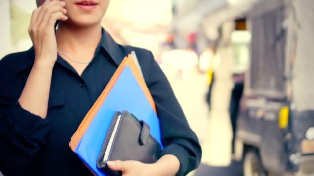 若い大人の実業家は、都市道路上の日の時間にスマートフォンを使用します。 - document点の映像素材/bロール