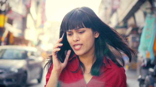 young adult businesswoman uses smartphone at day time on city road. - distraught stock videos & royalty-free footage