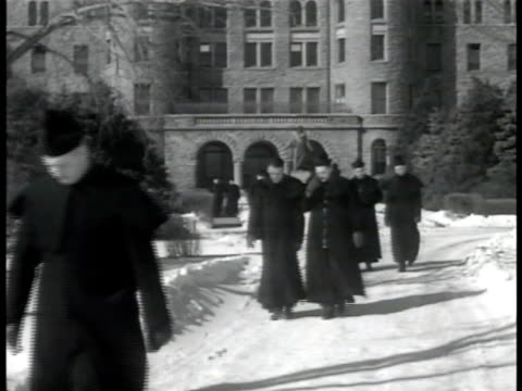 vidéos et rushes de young adult catholic male priests in skull caps walking from building in snow, possibly seminary, seminarians. young priests in conversation by... - religion