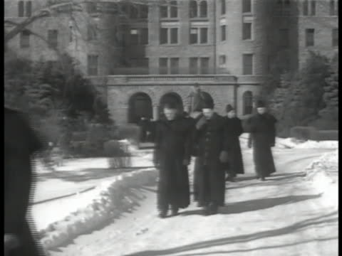young adult catholic male priests in skull caps walking from building in snow, possibly seminary, seminarians. young priests in conversation by... - priest stock videos & royalty-free footage