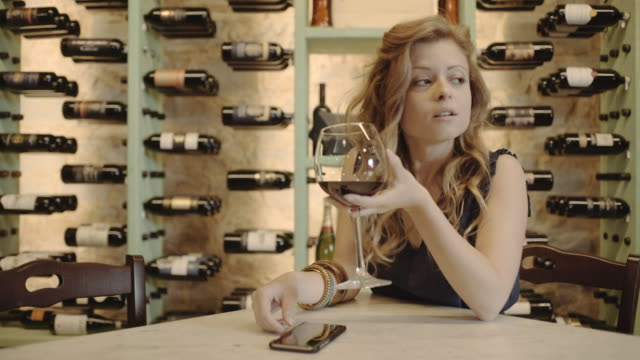 young adult checking smart phone at wine bar - wine bar stock videos & royalty-free footage