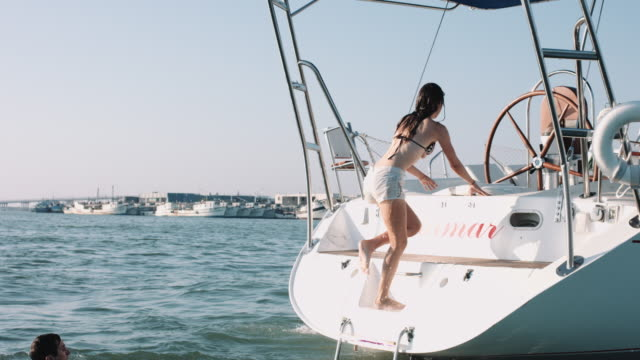 Young adult couple climbing on sailboat at sea