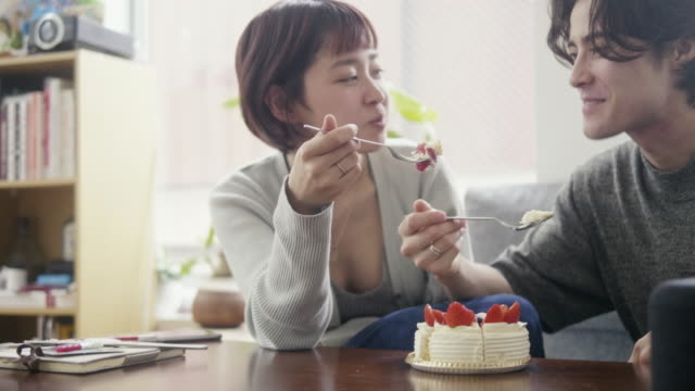 young adult couple eating japanese strawberry sponge cake on christmas - heterosexual couple stock videos & royalty-free footage