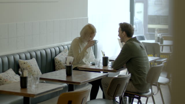 young adult couple having a good time together in cafe restaurant and drinking coffee at table - お食事デート点の映像素材/bロール