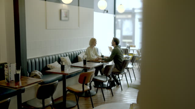 young adult couple having a good time together in empty cafe restaurant - cafe stock videos & royalty-free footage