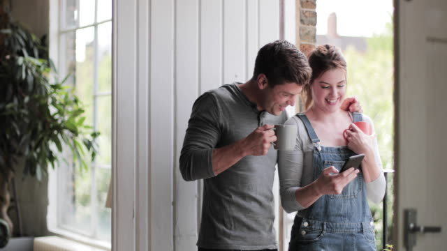 young adult couple having morning coffee and checking smartphone - dungarees stock videos & royalty-free footage