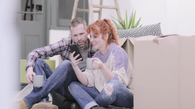 young adult couple in new home on smart phone - decoration stock videos & royalty-free footage