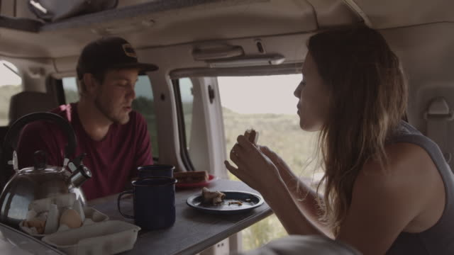 young adult couple inside campervan eating breakfast and drinking coffee on summer road trip - boyfriend stock videos & royalty-free footage